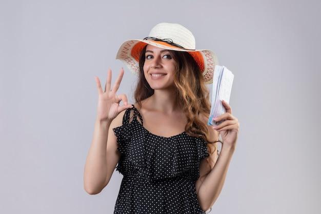 Jonge mooie reiziger meisje in jurk in polka dot in zomer hoed bedrijf vliegtickets glimlachend vrolijk doen ok teken staande op witte achtergrond