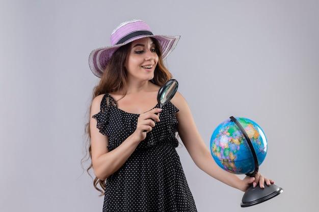Jonge mooie reiziger meisje in jurk in polka dot in zomer hoed kijken door vergrootglas met glimlach op gezicht staande op witte achtergrond