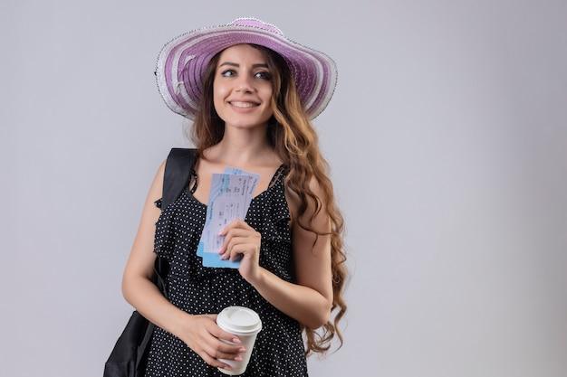 Jonge mooie reiziger meisje in zomer hoed met rugzak houden vliegtickets glimlachend vrolijk blij en positief staande op witte achtergrond