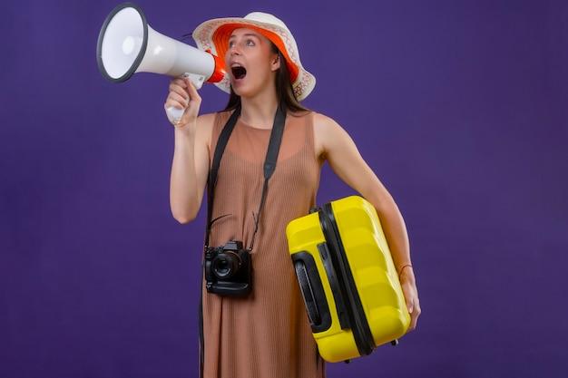 Jonge mooie reiziger vrouw in zomer hoed met gele koffer en camera schreeuwen naar megafoon staande over paarse achtergrond
