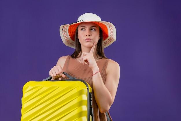 Jonge mooie reiziger vrouw in zomer hoed met gele koffer opzij kijken met vinger in de buurt van kin denken twijfels staande over paarse achtergrond