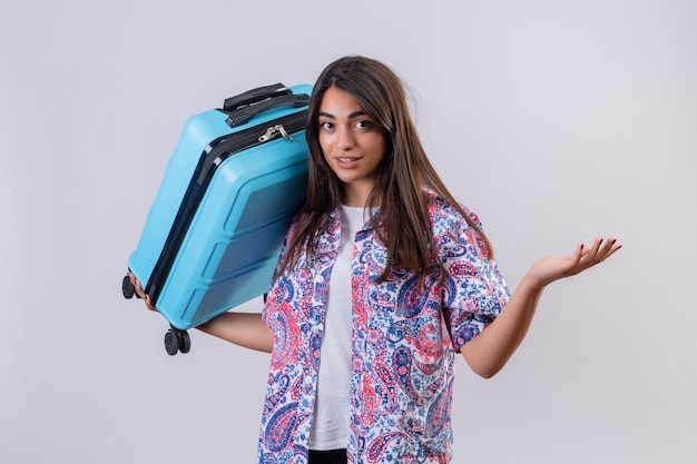 Jonge mooie reiziger vrouw met koffer op zoek verward gebaren met de hand en uitdrukking als het stellen van een vraag staande op een witte achtergrond