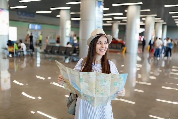 Jonge, mooie reizigerstoerist met een hoed die een papieren kaart vasthoudt, een route zoekt en wacht in de lobby op de internationale luchthaven