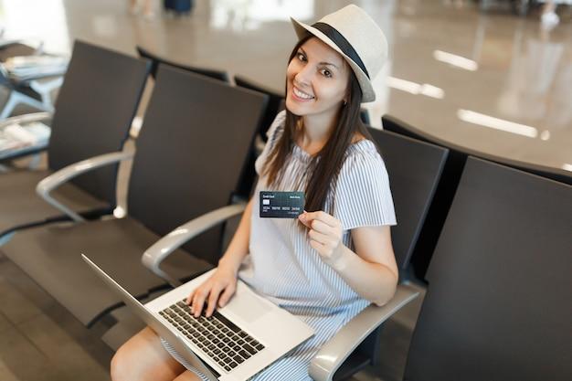 Jonge, mooie reizigerstoeristenvrouw die op laptop werkt, creditcard vasthoudt terwijl ze wacht in de lobby op de internationale luchthaven