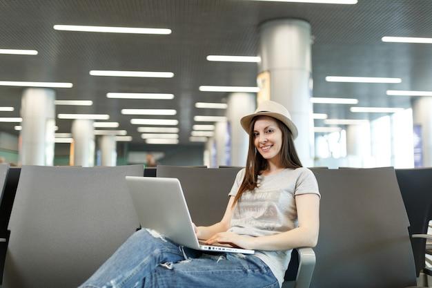 Jonge mooie reizigerstoeristenvrouw met hoed die aan laptop werkt terwijl ze wacht in de lobby op de internationale luchthaven