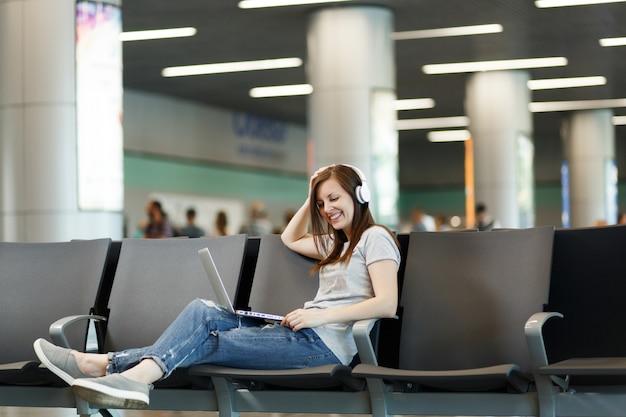 Jonge, mooie reizigerstoeristenvrouw met koptelefoon die muziek luistert die op laptop werkt, wacht in de lobby op de internationale luchthaven
