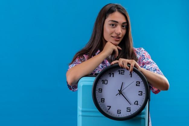 Jonge mooie reizigersvrouw die blauwe koffer en ronde klok met hand op kin houdt die en over blauwe muur denkt wacht