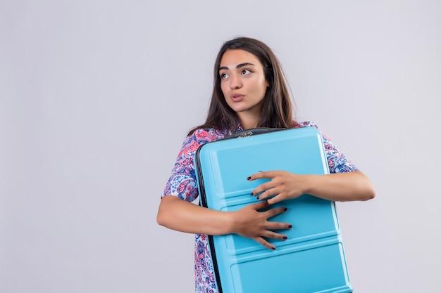 Jonge mooie reizigersvrouw die blauwe koffer koestert die opzij met positieve uitdrukking op gezicht kijkt die zich over witte achtergrond bevindt