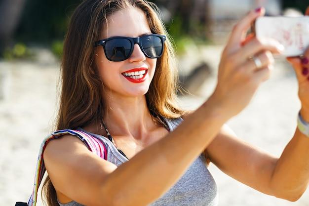 Jonge mooie reizigersvrouw die foto's maakt op zonnig strand, alleen reist met rugzak in warm tropisch land, casual outfit, fitnesslichaam, avontuurlijke stemming.