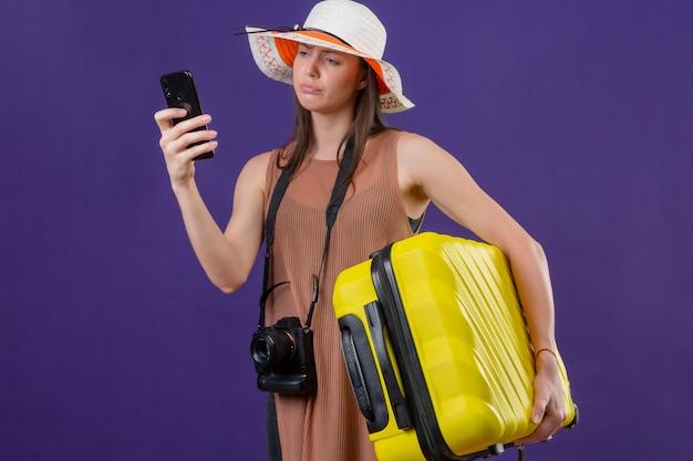 Jonge mooie reizigersvrouw die in de zomerhoed met gele koffer en fotocamera het scherm bekijken oh haar mobiele telefoon met ongelukkig gezicht
