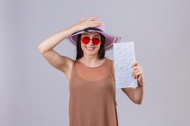 Jonge mooie reizigersvrouw die in de zomerhoed rode zonnebril dragen die vliegtickets houden die met gelukkig gezicht glimlachen die zich over witte achtergrond bevinden