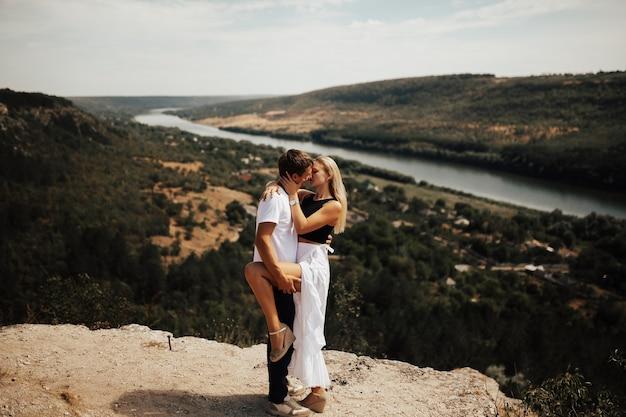 Jonge mooie romantische paar knuffelen en zoenen op de achtergrond van een rivier en bos, bergen in zonnige zomerdag