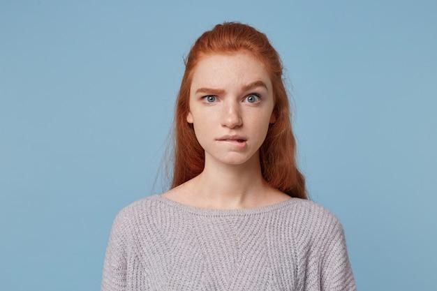 Jonge mooie roodharige tiener meisje kijkt bezorgd in paniek verbaasd