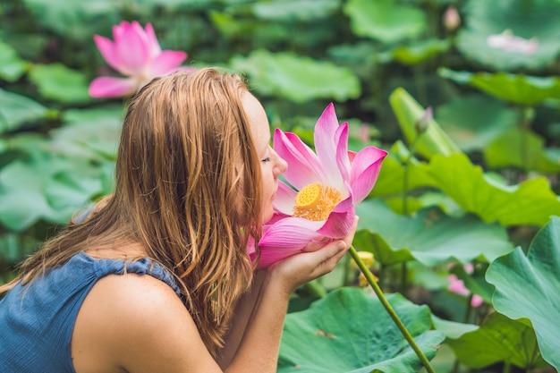 Jonge mooie roodharige vrouw bewondert de lotusbloem die het in haar handen houdt
