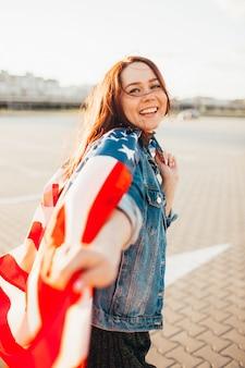 Jonge mooie roodharige vrouw gewikkeld met nationale vlag van de verenigde staten over zonneschijn.