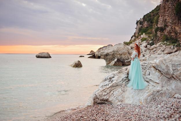 Jonge mooie roodharige vrouw in een luxe jurk staande op een rotsachtige kust van de adriatische zee