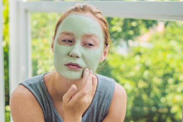 Jonge mooie roodharige vrouw met een reinigend masker van cosmetische klei op haar gezicht genieten van een frisse smoothie en ontspanning