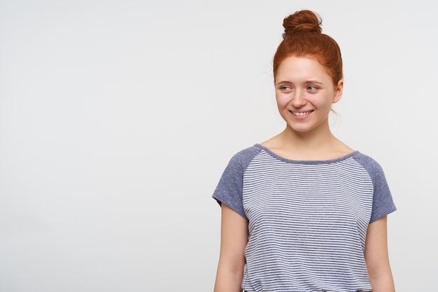 Jonge mooie roodharige vrouw met natuurlijke make-up, gekleed in een blauw gestreept t-shirt terwijl ze over een witte muur staat, positief opzij kijkend met een charmante glimlach