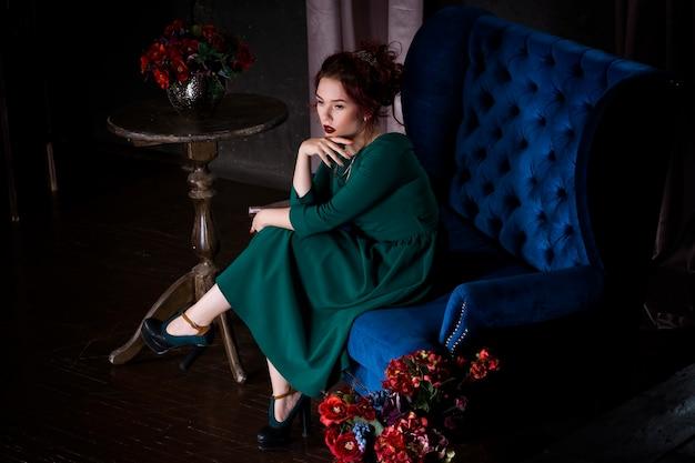 Jonge mooie roodharige vrouw met professionele make-up in groene jurk die zich voordeed op blauwe sofa