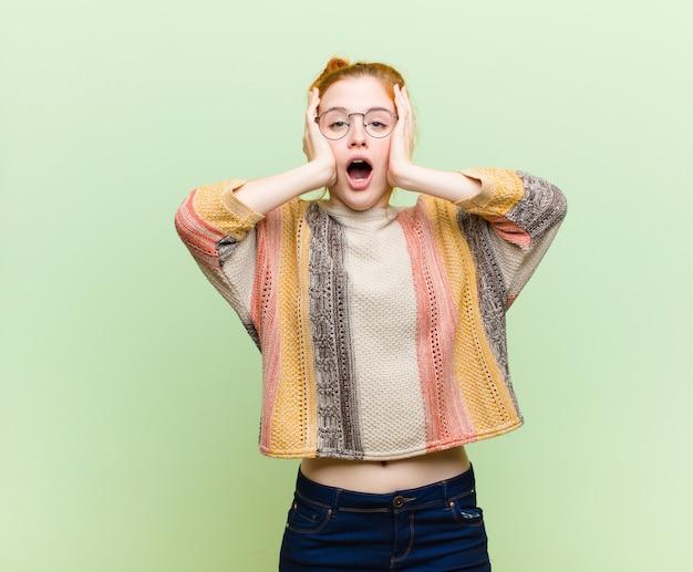 Jonge mooie roodharige vrouw op zoek onaangenaam geschokt, bang of bezorgd, mond wijd open en beide oren bedekkend met handen tegen groene muur