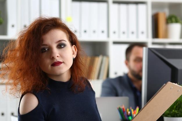 Jonge mooie roodharige vrouw zitten aan tafel in het kantoor in het kabinet van haar baas