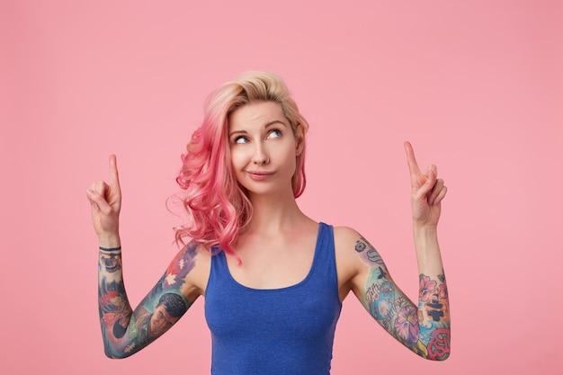 Jonge mooie roze harige dame in blauw t-shirt met opgeheven armen, twijfelt iets, kijkt op en wil je aandacht vestigen door met de vingers op de kopie ruimte te wijzen, staande.