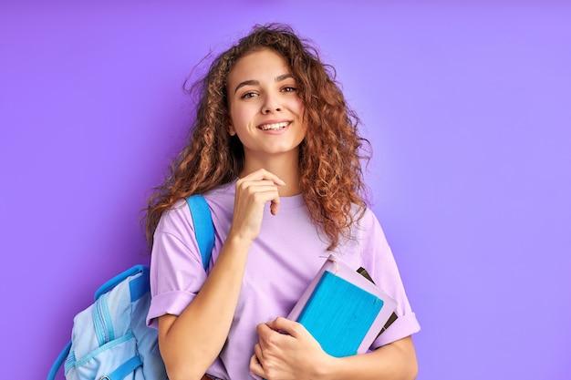 Jonge mooie school meisje met krullend haar enthousiast over studeren, voorbereiden op school of universiteit, geïsoleerde paarse ruimte