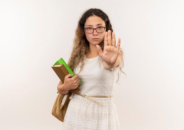 Jonge mooie schoolmeisje bril en rug tas houden boeken kijken en gebaren stop bij camera geïsoleerd op een witte achtergrond met kopie ruimte