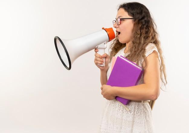 Jonge mooie schoolmeisje bril en rug tas staande in profiel te bekijken houden boeken praten door spreker geïsoleerd op de achtergrond met kopie ruimte