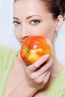 Jonge mooie sensualiteitsvrouw met appel - binnen
