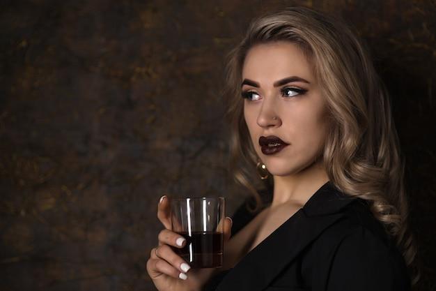 Jonge mooie sexy blonde in een zwarte jas en ondergoed met glas whisky op een donkere achtergrond