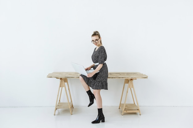 Jonge mooie sexy blonde vrouw in glazen zitten met een laptop op tafel