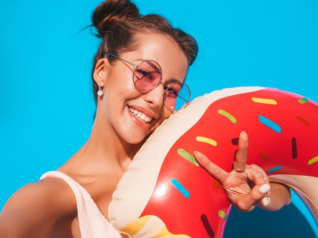 Jonge mooie sexy glimlachende hipster vrouw in zonnebril. met donut lilo opblaasbaar matras. gek worden.
