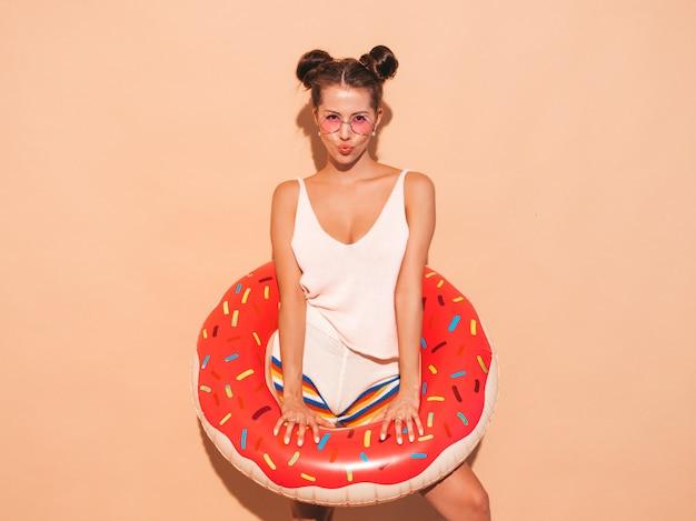 Jonge mooie sexy glimlachende hipster vrouw in zonnebril. met donut lilo opblaasbaar matras. positieve vrouw wordt gek. grappig model