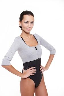 Jonge mooie sexy glimlachende modieuze die vrouw op wit in grijs jersey wordt geïsoleerd