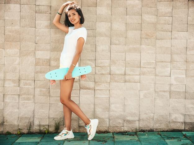 Jonge mooie sexy lachende hipster vrouw in zonnebril. trendy meisje in zomer t-shirt en korte broek. positieve vrouw met blauwe cent skateboard poseren in de straat in de buurt van muur