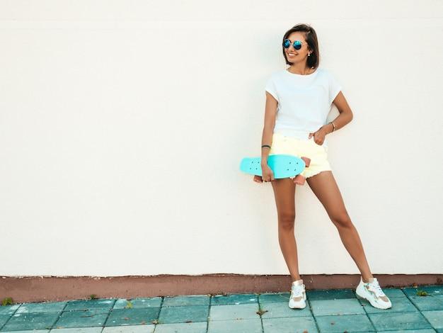 Jonge mooie sexy lachende hipster vrouw in zonnebril. trendy meisje in zomer t-shirt en korte broek. positieve vrouw met blauwe cent skateboard poseren in de straat in de buurt van witte muur