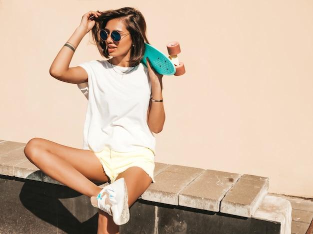 Jonge mooie sexy lachende hipster vrouw in zonnebril. trendy meisje in zomer t-shirt en korte broek. positieve vrouw met blauwe cent skateboard poseren op de straat achtergrond