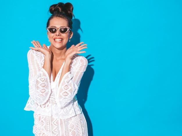 Jonge mooie sexy lachende vrouw met griezelige kapsel. trendy meisje in casual zomer witte hipster pak kleding in zonnebril. heet model dat op blauw wordt geïsoleerd. geschokt en verrast met handen dichtbij gezicht
