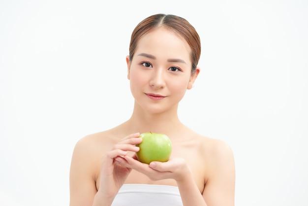 Jonge mooie sexy meisje blote schouders en nek, houdt grote groene appel vast om te genieten van de smaak en zijn op dieet, gezond eten en biologisch voedsel, verleiding voelen