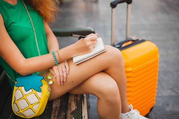 Jonge mooie sexy vrouw, hipster outfit, reiziger, oranje koffer, aantekeningen maken in reisdagboekboek, zomervakantie, avontuur, reis, kleurrijk, handen schrijven, pen, details close-up