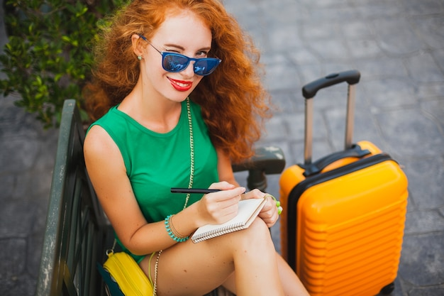 Jonge mooie sexy vrouw, hipster outfit, rood haar, reiziger, groene top, oranje koffer, aantekeningen maken, reisdagboekboek