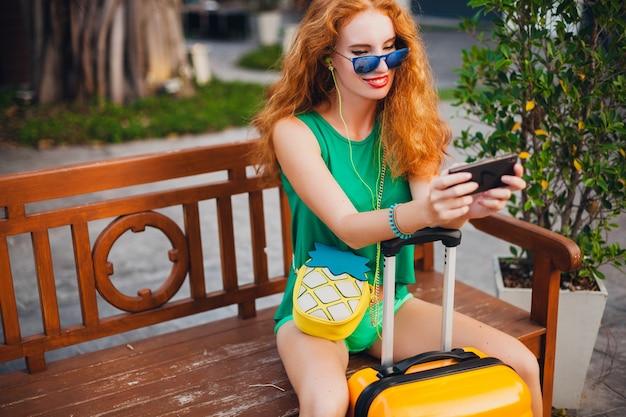 Jonge mooie sexy vrouw, hipster stijl, rood haar, reiziger, groene top, korte broek, oranje koffer, zomervakantie, reizen, zittend, wachten, smartphone vasthouden, zonnebril, muziek luisteren, koptelefoon