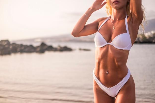 Jonge mooie sexy vrouw in bikini badpak, tropisch eiland, zomervakantie, resort fashion stijl, zand, slank, gelooid, strand, uitzicht vanaf de achterkant, buit, vredesteken tonen, positieve stemming, gelukkig, heupen