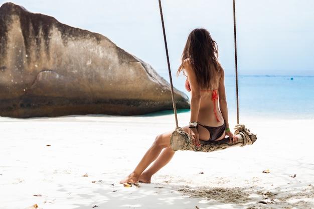 Jonge mooie sexy vrouw in bikini zwembroek zittend op schommel op tropisch eiland, zomervakantie, resort mode-stijl, zand, slanke benen, gelooid, zonnebril, strand, glimlachen, gelukkig, positief
