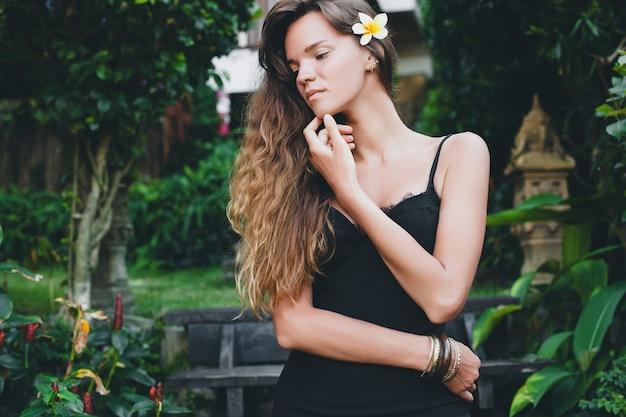Jonge mooie sexy vrouw in tropische tuin, zomervakantie in thailand, slank mager gebruind lichaam, kleine zwarte jurk met kant, natuurlijke look, sensueel, ontspannen,