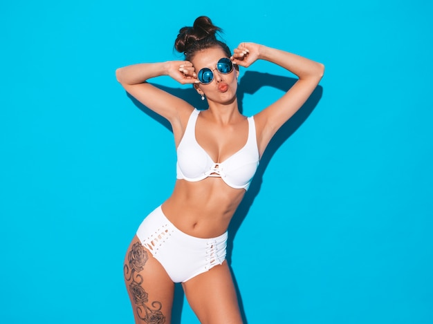 Jonge mooie sexy vrouw met lijkenetende kapsel. trendy meisje in casual zomer wit zwempak in zonnebril. heet model geïsoleerd op blauw. maakt eendgezicht