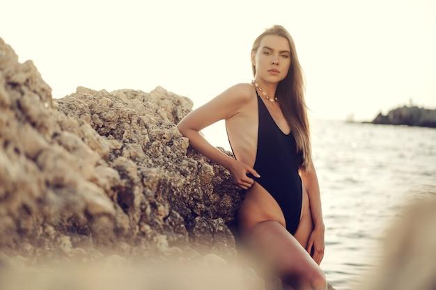 Jonge mooie sexy vrouwelijke model in zwarte bikini staande in zee in de buurt van enorme rots