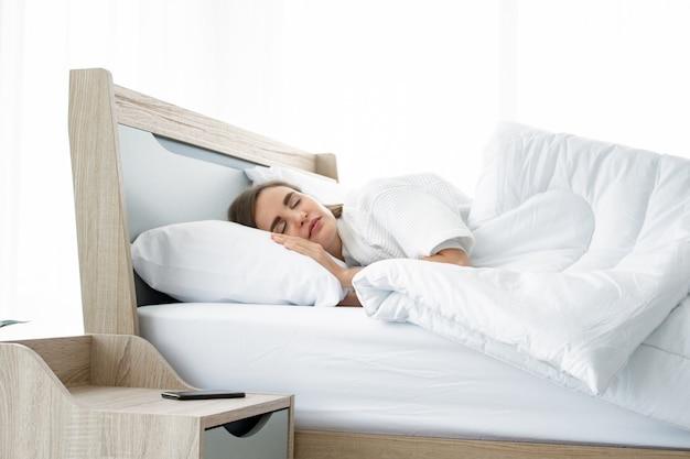 Jonge mooie slaap in het bed thuis.