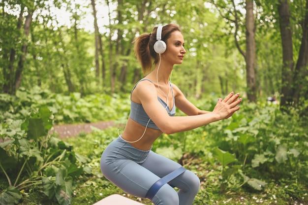Jonge mooie slim fit meisje in blauwe sportkleding met grote witte koptelefoon doen oefening met fitness training gom in het park